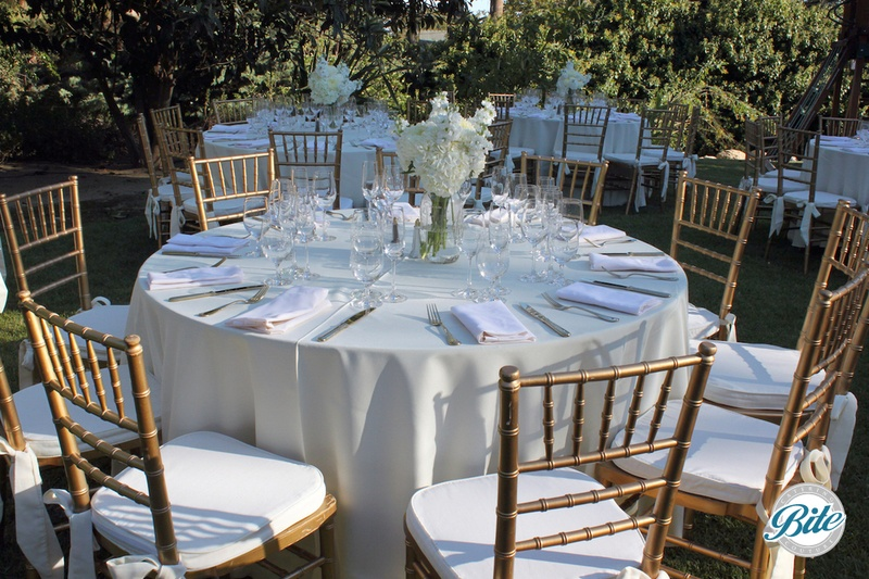 Elegant table setting in white and gold with client floral arrangement
