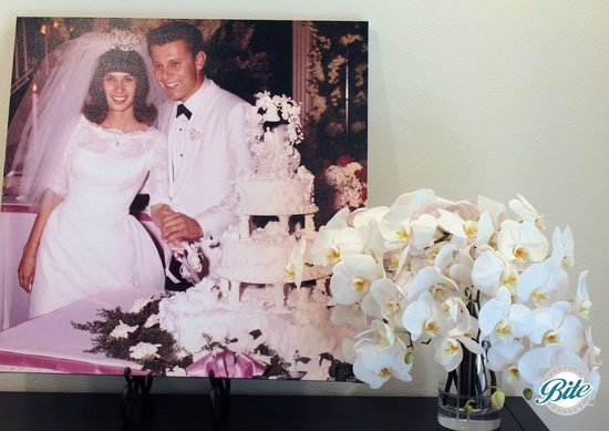 The happy couple on their wedding day 50 years earlier next to a lovely floral arrangement