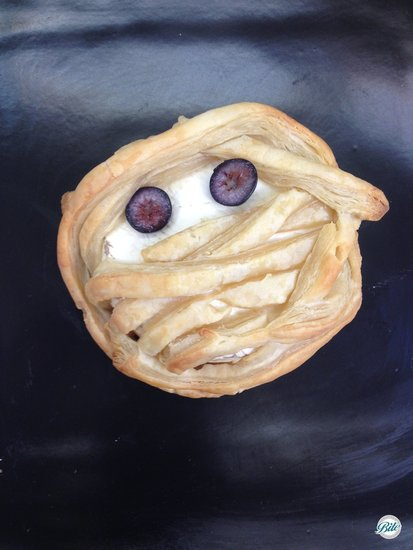 A delicious baked brie wrapped with jam and puf pastry to look like a mummy served with fruit and crackers