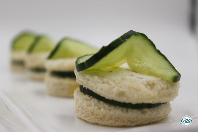 Round cucumber sandwiches with cucumber slice on top from Bite Catering's full-service high tea menu