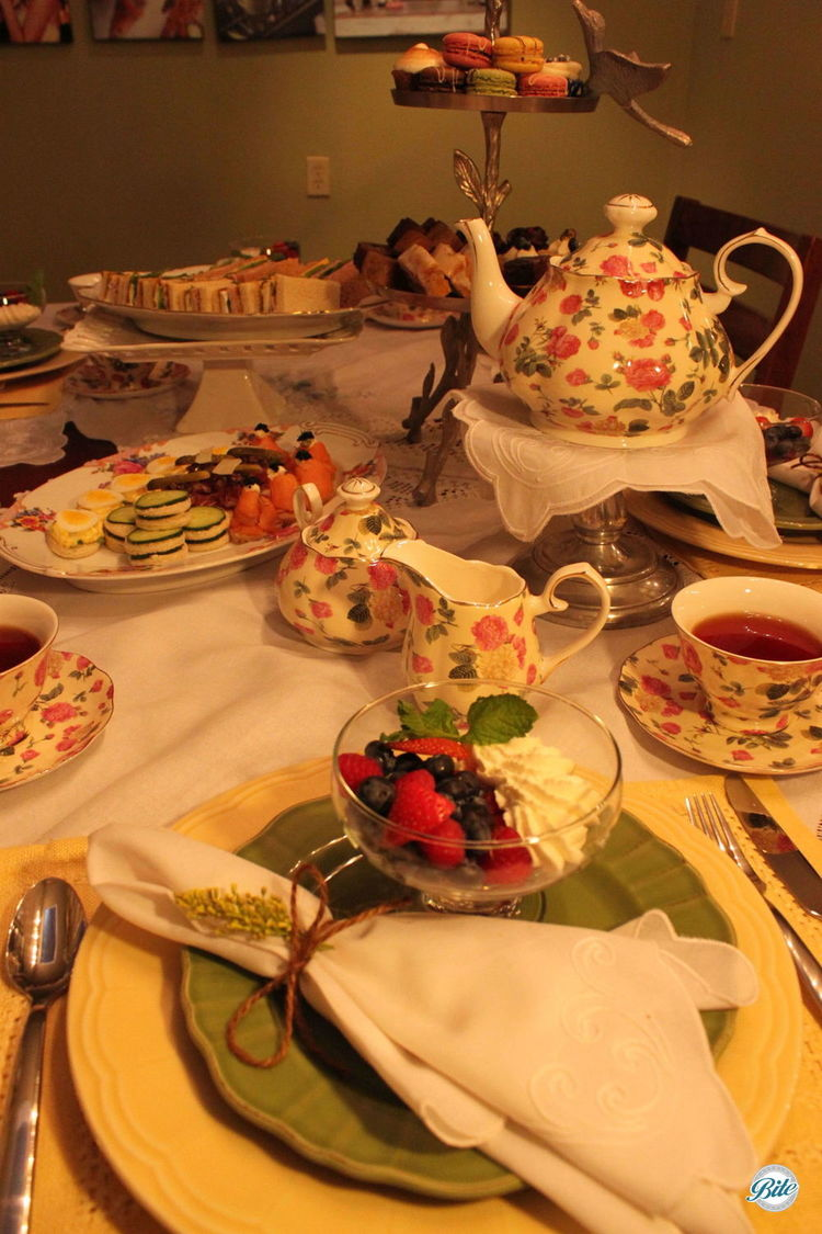Flowered tea pots on table surrounding mixed berry and cream starter course with tea sandwiches in center