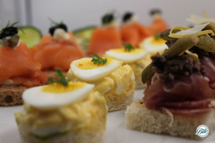 From our full service menu, open face tea sandwiches add color and pizzazz. Smoked salmon with caviar, egg salad with sliced egg and micro basil, and prosciutto with pickle.