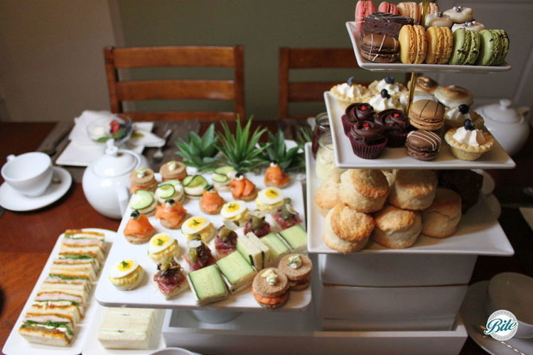 Tea service on white risers. Classic tea finger sandwiches.  Open faced tea sandwiches, scones with jam and clotted cream, cupcakes, macaron, and tea breads