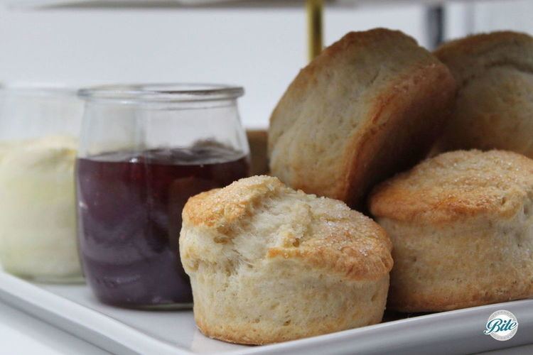 Scones on white riser with clotted cream and jam in glass containers