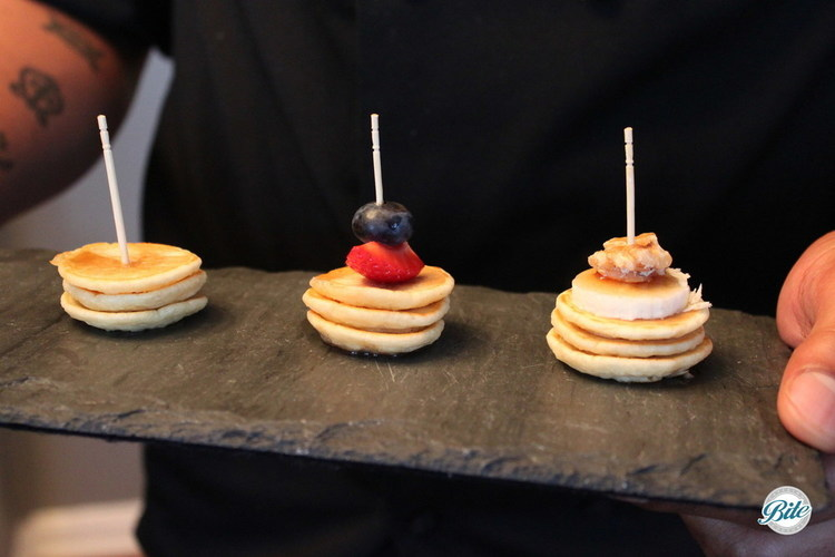 3 mini pancakes in triple stack with toothpick.  Plain, mixed berry (strawberry and blueberry), and banana walnut.