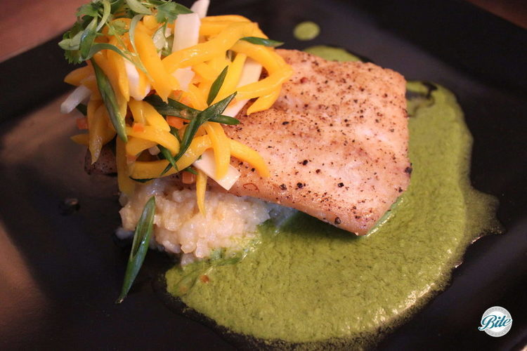 Mahi mahi plated w/ pineapple risotto, coconut mango salad, coconut milk salsa verde on a black square plate