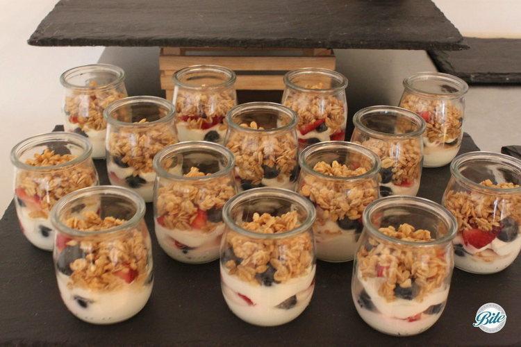 Granola parfait cups on slate display. Granola, strawberry, blueberry, honey, and yogurt.