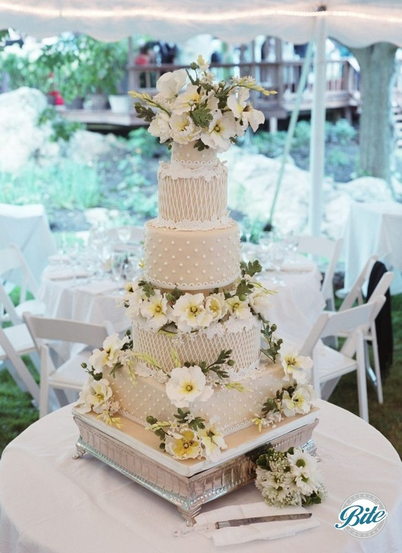 5 tier white wedding cake with yellow an green accents, and sugar flowers, displayed for outdoor reception