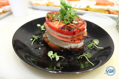 Plated stacked caprese salad.  Heirloom tomatoes, mozzarella, balsamic vinegar, garnished with watercress.