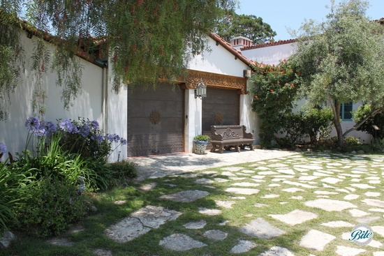 Stone courtyard with view of house and garage