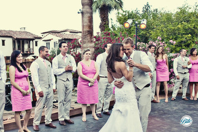 Outdoor wedding with the couple having their first dance outdoors. The wedding party wore pink and and grey