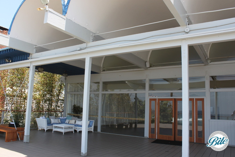 A large deck with a roof providing shaded areas @ the Malibu West Beach Club