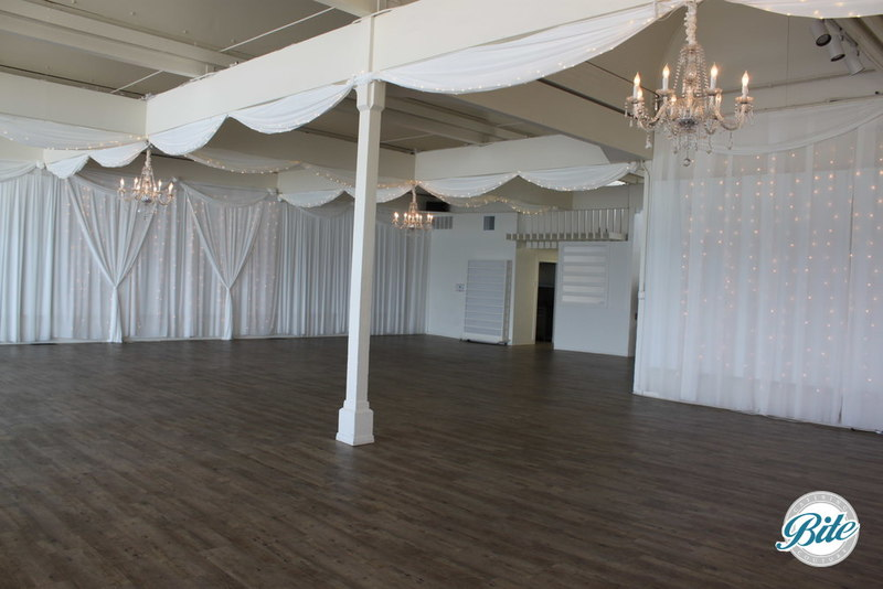 Looking across the room, you can see the substantial space to host an event and the ambiance possible with lighting, draping, and chandeliers