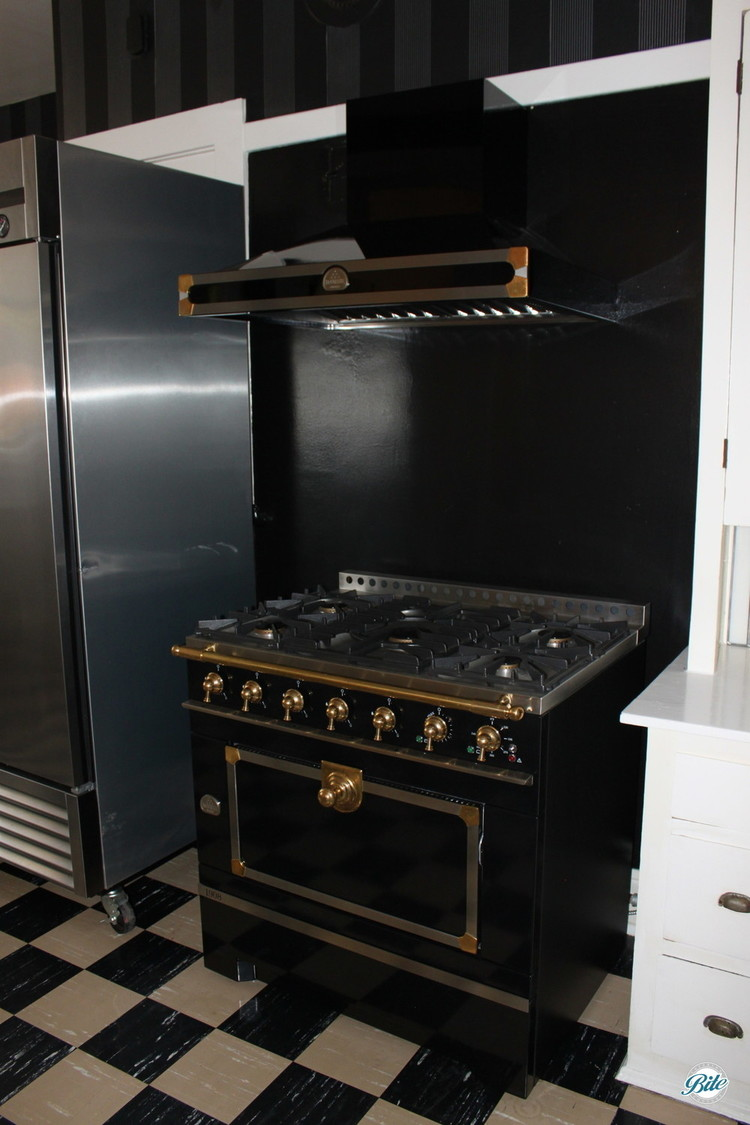 A vintage ebony La Cornue range and hood in the Wattles Mansion kitchen highlights a handmade kitchen focal point with manufacturing beginning in 1908