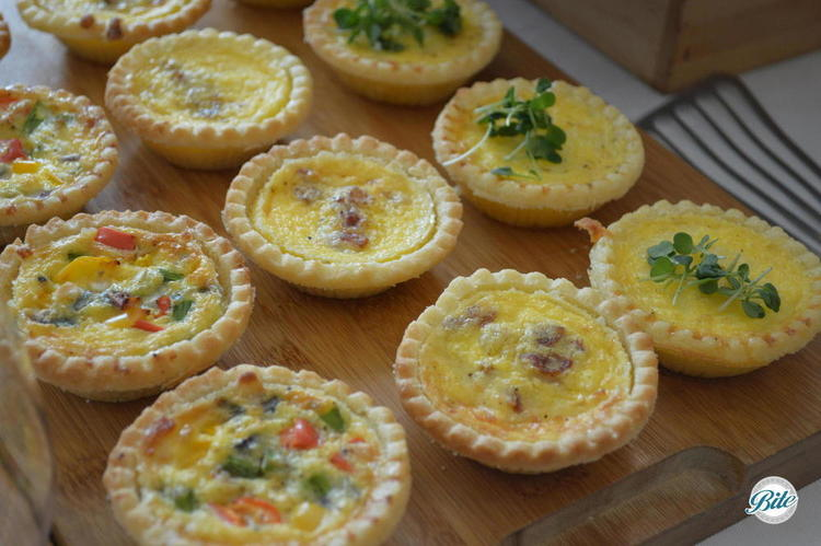 Assorted mini quiches on cutting board - cheese, seasonal vegetable and quiche lorraine