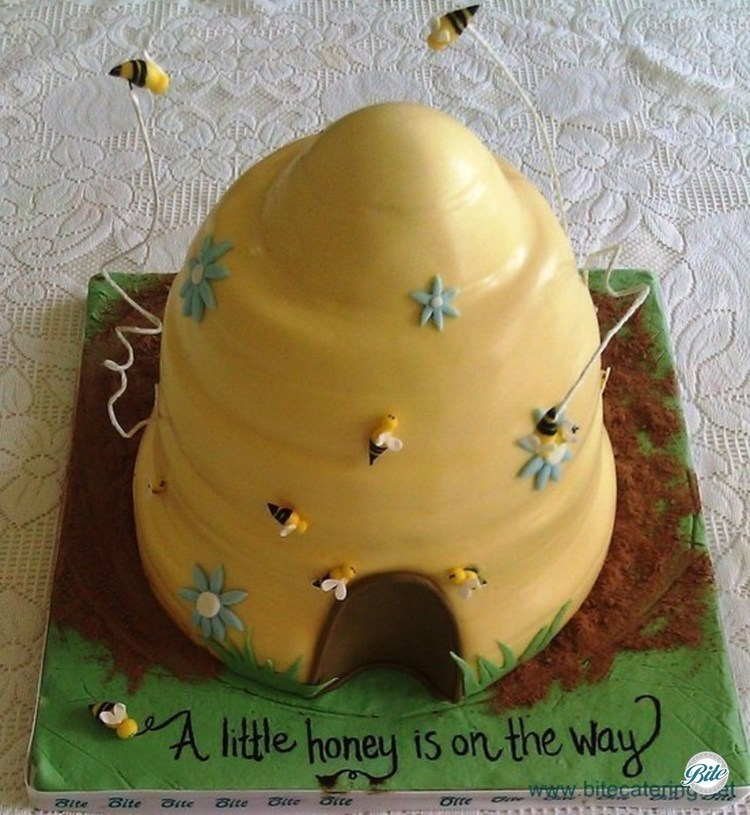 Yellow and green beehive designed cake with grass, bumble bees, grass and flowers.