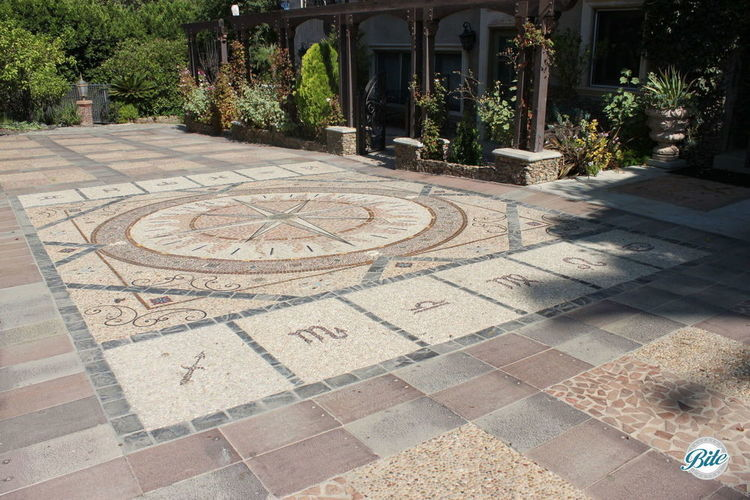 Beautiful mosaic compass is the focal point of the driveway in front of the residence