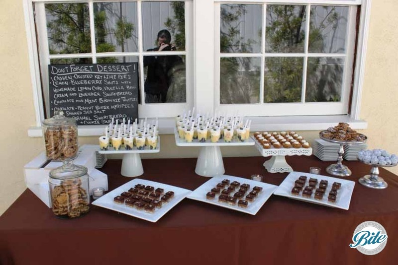 Dessert display with beautiful spread of Lemon curd and blueberry shots, almond caramel bars, oatmeal cream cheese cookie sandwich on shabby chic dishes