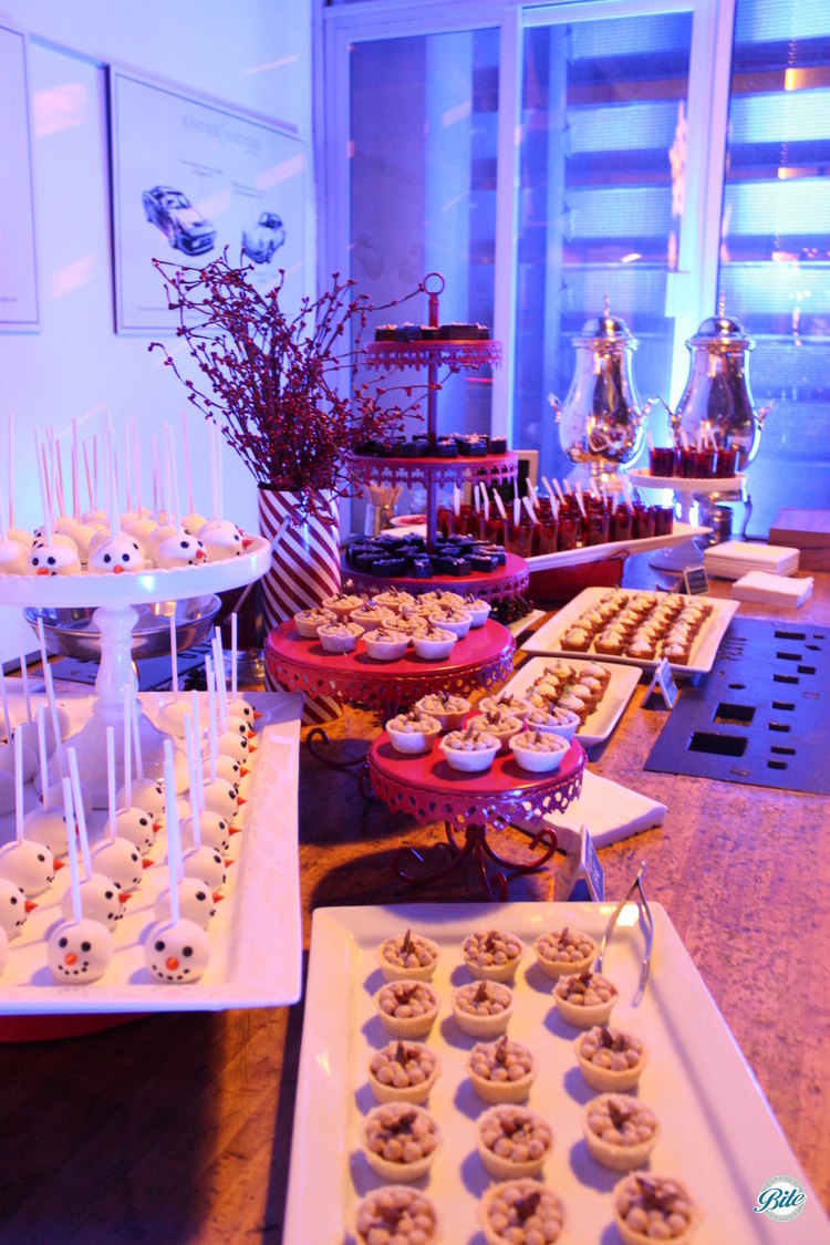 Dessert display table with snowman cake pops, pumpkin pie bites, mini key lime pie, chocolate peppermint brownies, sticky toffee pudding shots, coffee station