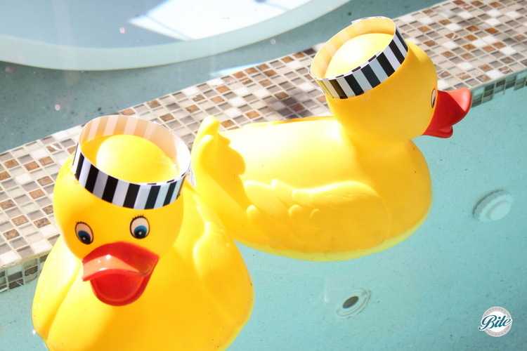 Rubber Duckys wearing black and white prison stripes in pool