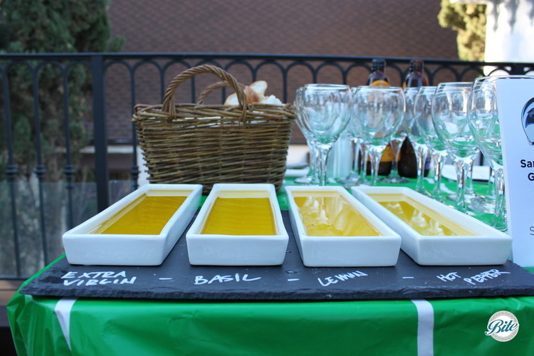 Flavored olive oils for an olive oil tasting with a freshly baked breadbasket in the background. Flavors include normal extra virgin olive oil and versions infused with basil, lemon, and hot pepper.