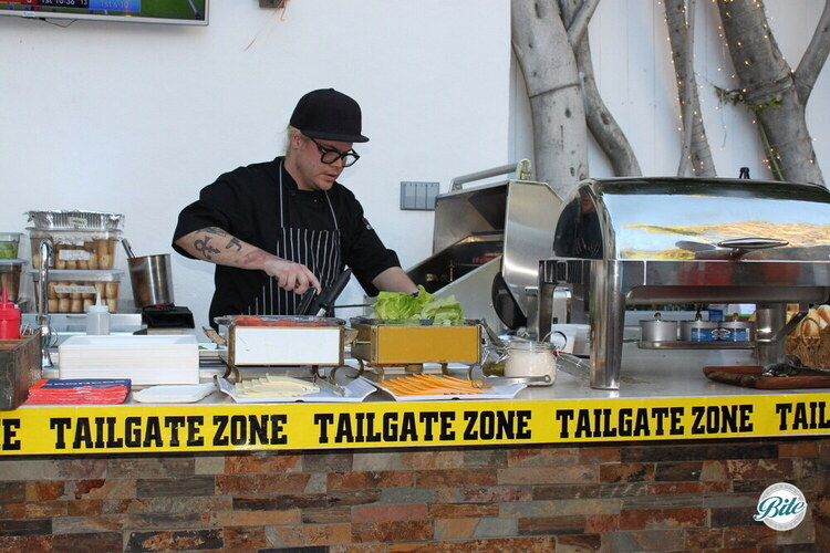 Tailgate Grill Station at Super Bowl party. Chef serving hot dogs and burgers off the grill w/ build-your own toppings and selection of buns