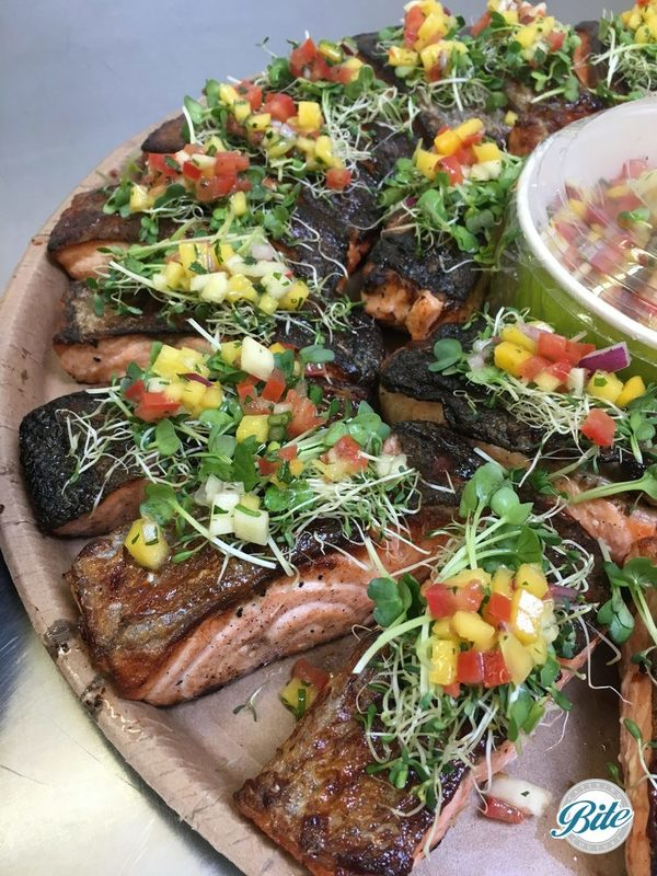 Crispy BBQ salmon, skin on baked salmon, baby sprouts salad and Tropical salsa. On delivery platter with additional tropical salsa garnish.