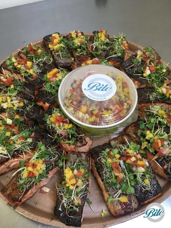 Crispy BBQ salmon, skin on baked salmon, baby sprouts salad and Tropical salsa.  On eco-friendly delivery tray.