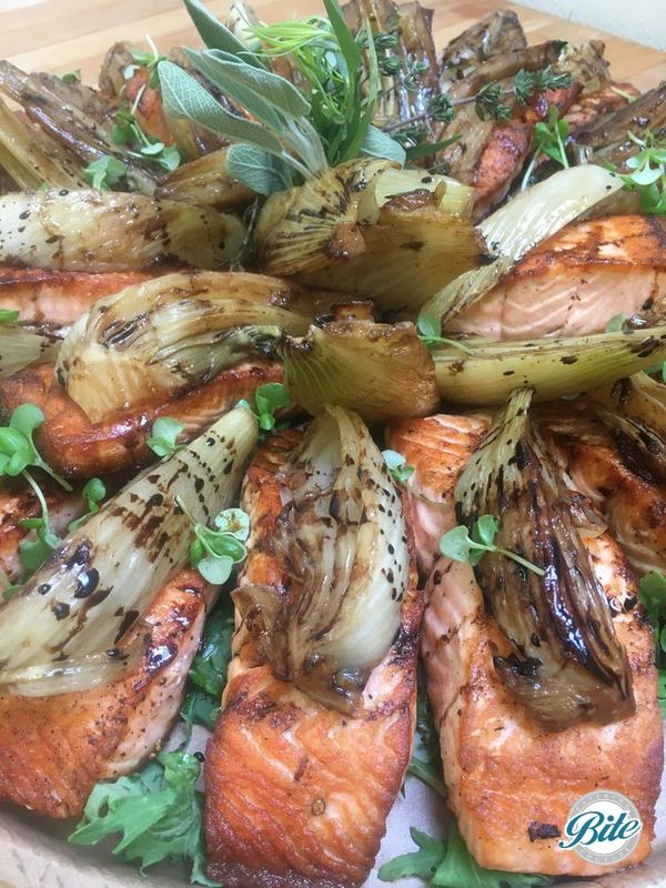 Pan-seared salmon with braised fennel & balsamic reduction. On delivery tray and garnished with flowers