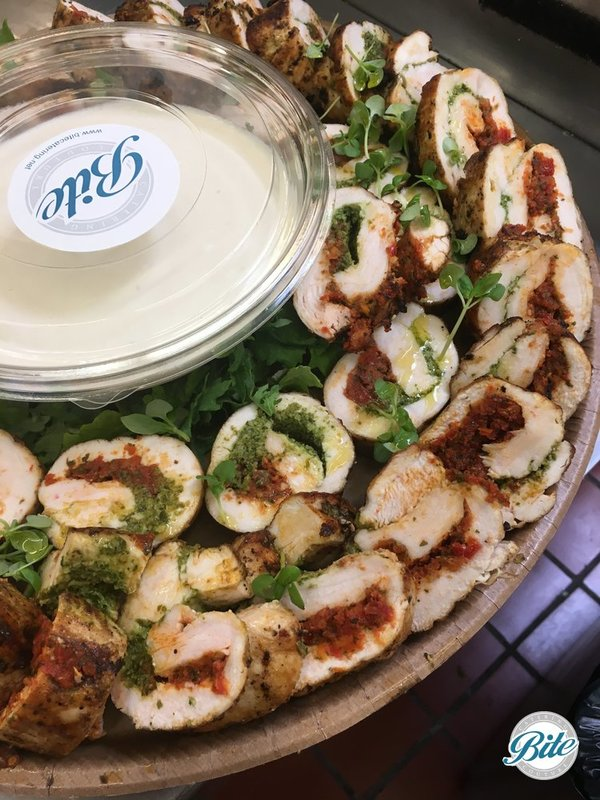 Chicken roll with a pesto duo: sundried tomatoes pesto, basil pesto and Creamy horseradish dipping sauce. On eco-friendly delivery tray,