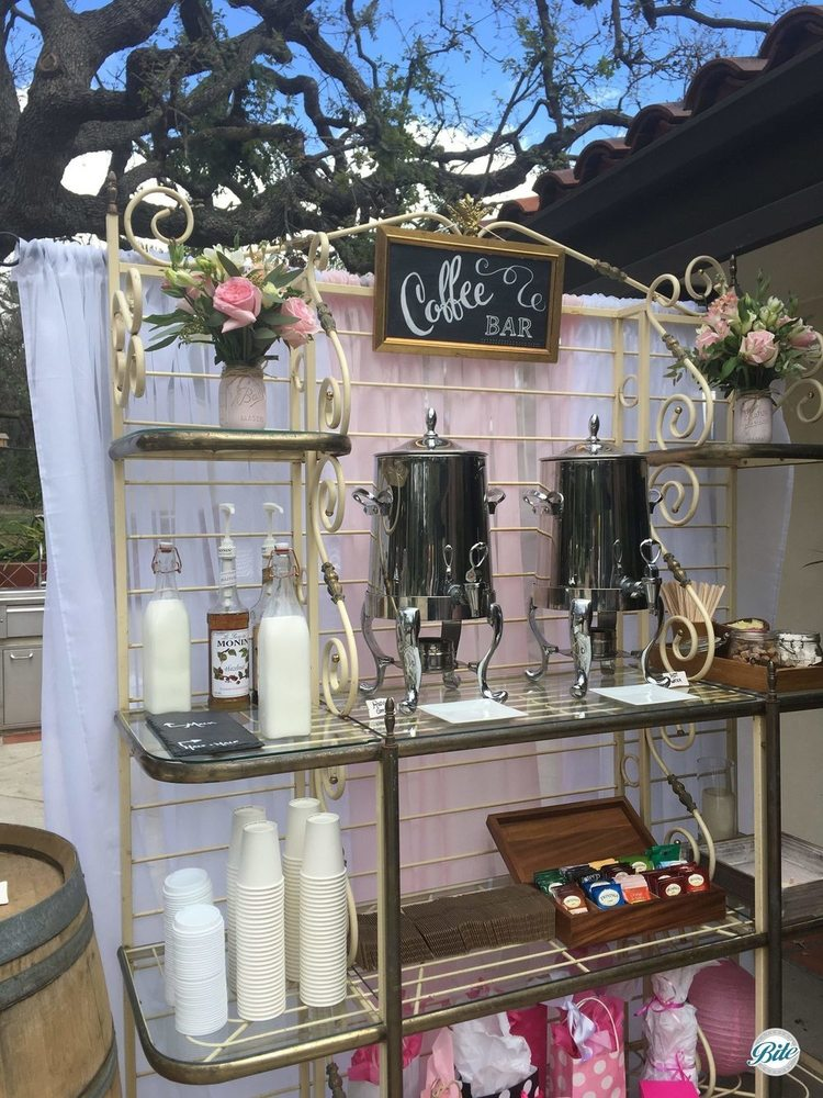 Coffee Bar display with chalkboard sign, rustic wine barrel, creamer, sugar, flavored syrups. White and pink backdrop with floral decor in mason jars