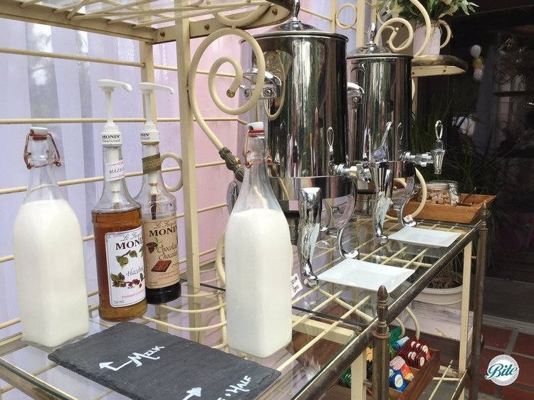 Coffee bar setup with coffee urns, flavored hazelnut and chocolate syrups, tea, milk, creamer