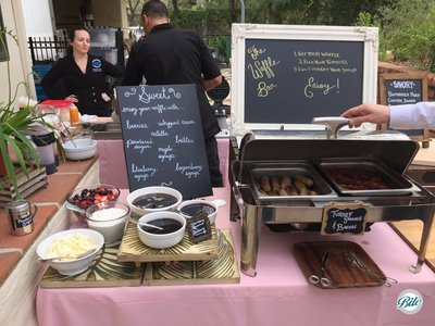 Waffle Bar with sweet and savory options. Toppings include berries, whipped cream, nutella, butter, maple syrup, boysenberry syrup, blueberry syrup, powdered sugar. Accompanied by Turkey Sausage and Bacon