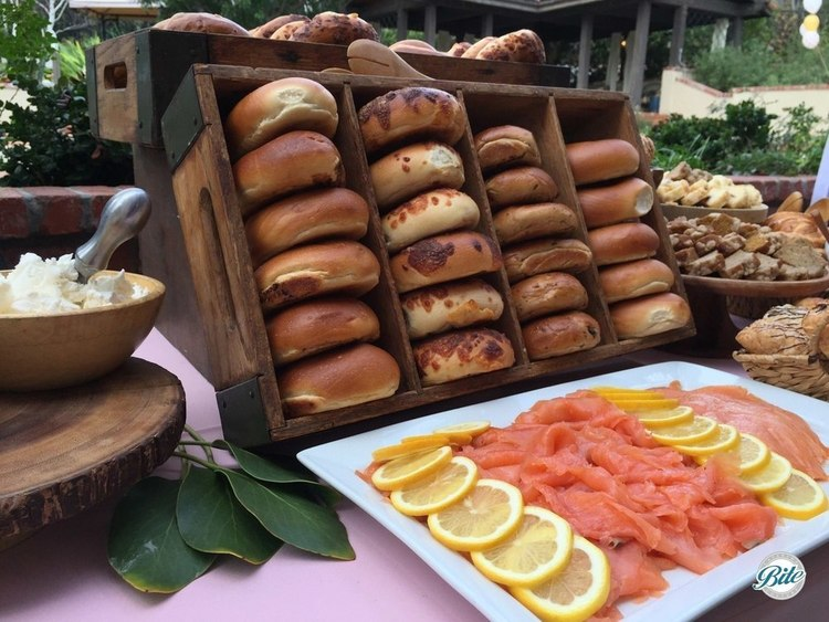 Bagels on display with smoked salmon and lemons. Flavored cream cheese and toppings on side