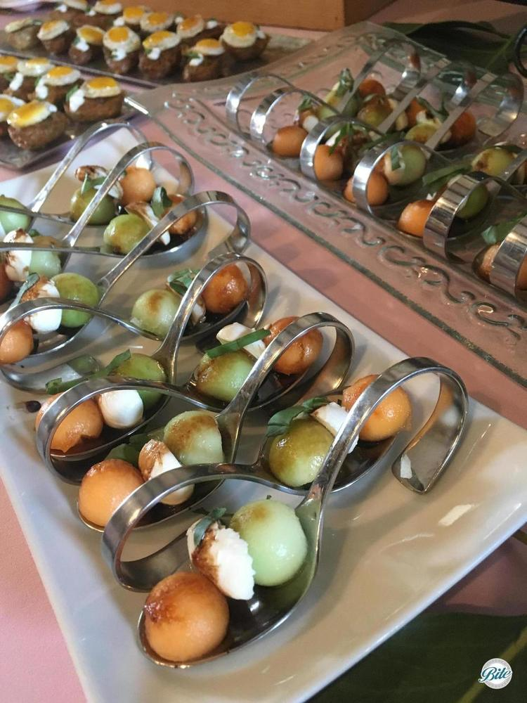 Melon spheres, fresh mozzarella, and micro basil served on individual metal spoons on a display