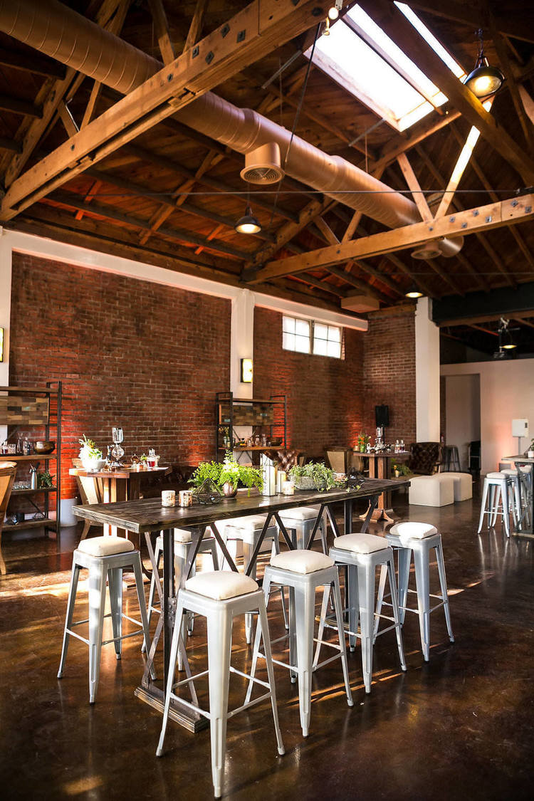 A view of the brick walls, high wooden ceilings and naturally lit space of At the P. This flexible setup was used for a networking and product launch event.