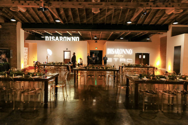 Cole space organized for a sleek corporate event including a seated dinner and access to a step and repeat and outdoor patio