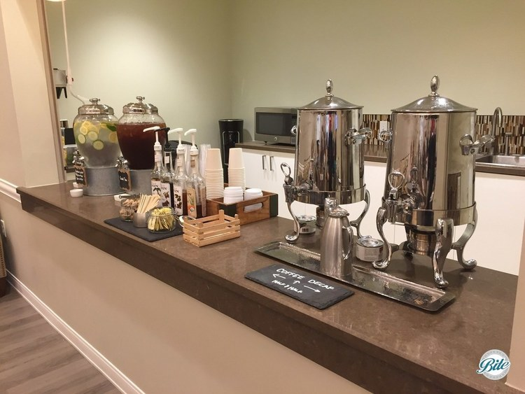 Coffee service in stainless steel urns with flavored shots and cucumber and lemon-infused water and ice tea