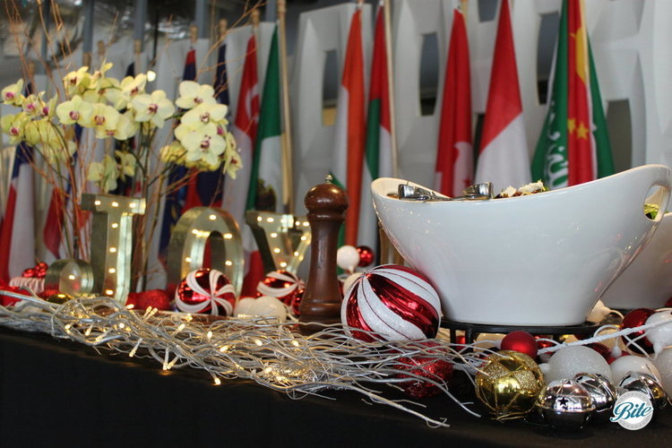 A festive holiday table with JOY in lights and numerous holiday ornaments