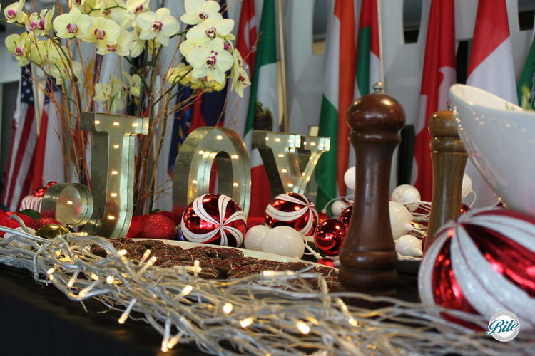 A closeup of a festive corporate holiday event table with JOY in lights and numerous holiday ornaments