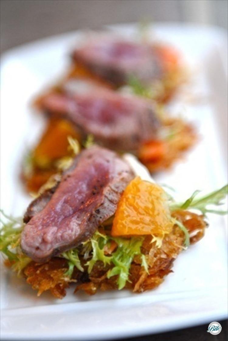 Crispy potato latke with micro salad, orange vinaigrette, fresh orange supreme, and seared duck