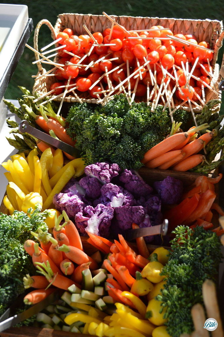 A colorful crudite basket with carrots, broccoli, summer squash, cucumber, peppers, and cherry tomatoes