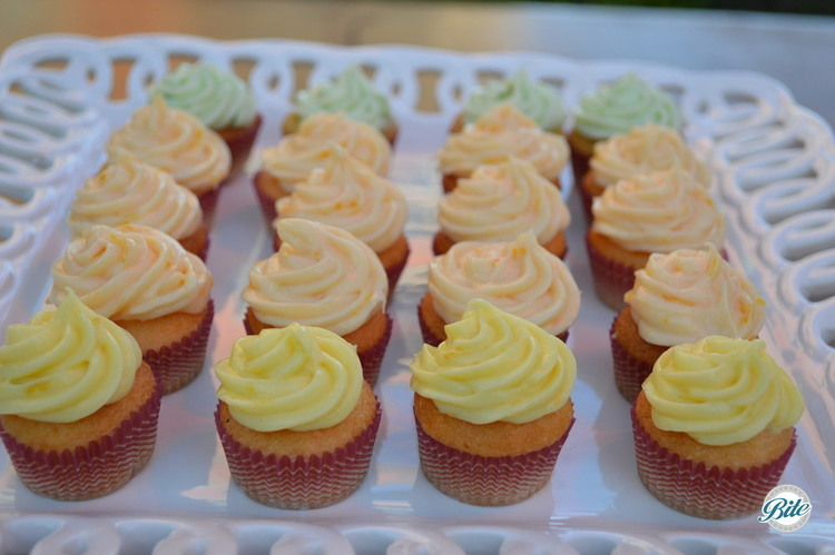 Citrus themed cupcakes with frosting on a white ceramic tray.