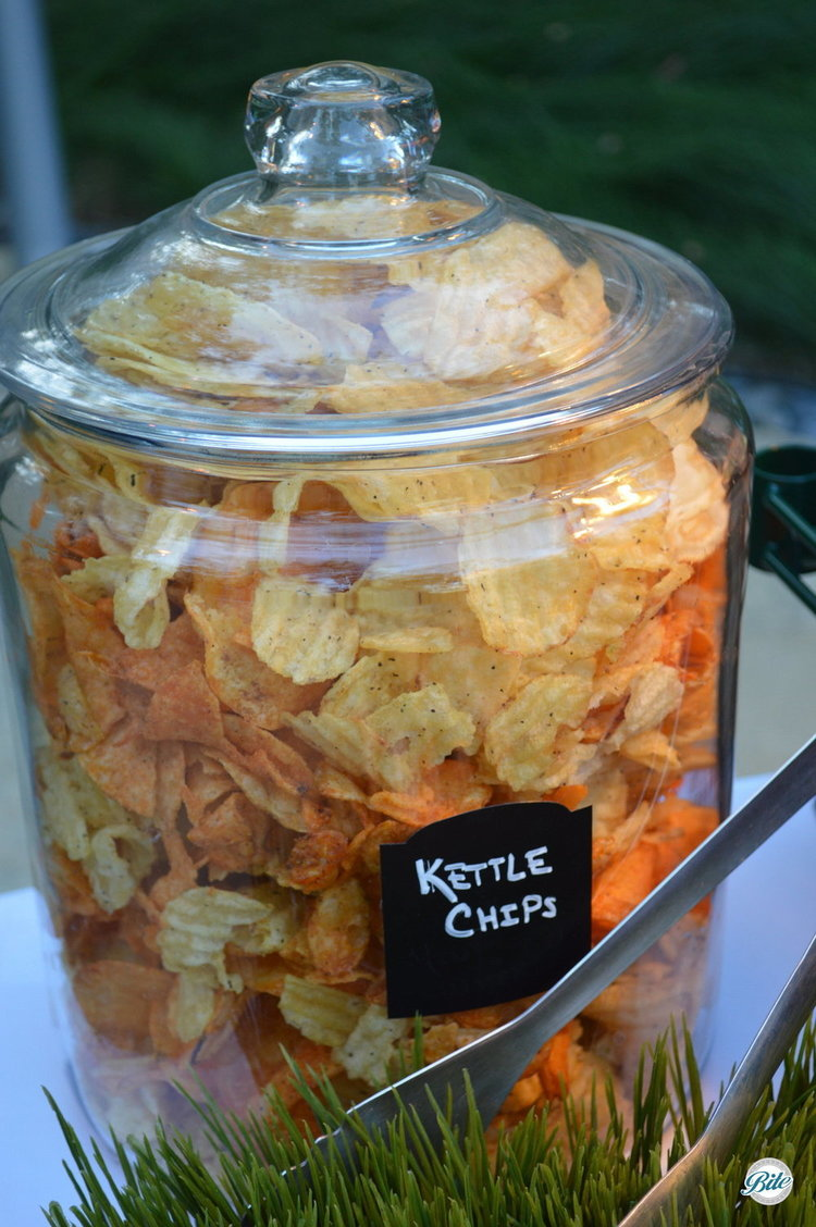 Kettle chips of assorted colors and flavors in glass jar on slider bar