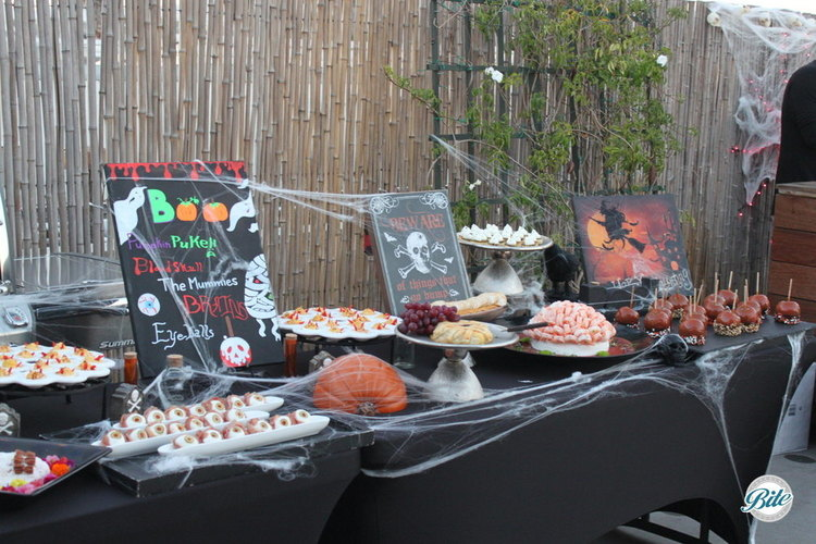 Halloween display with eyeballs, mummy, brains, ghost canapes, and candied apples. Decor elements include decorated chalkboard signs, halloween elements, and lots of cobwebs.