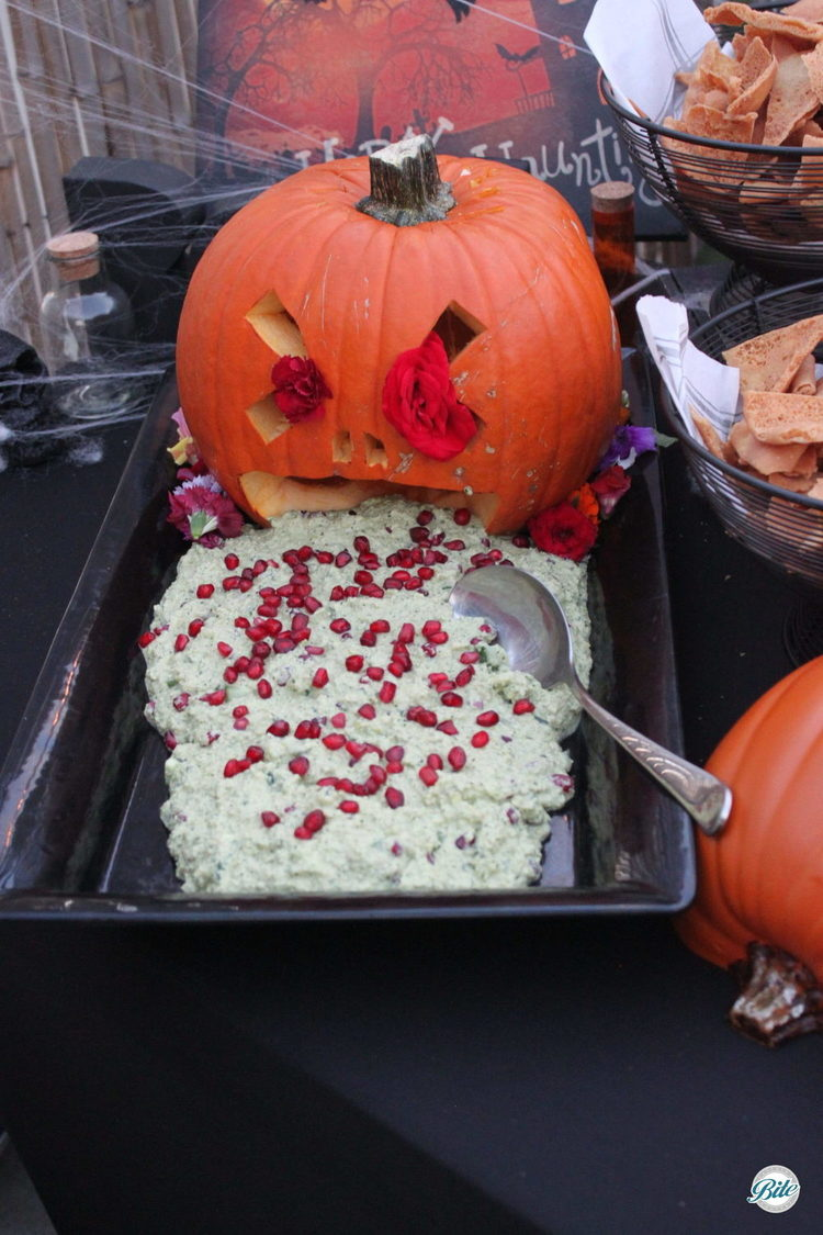 Hand-carved puking pumpkin with edamame hummus and pomegranate seeds.  Goes great with fried bat wings (pita chips)!  Grossly delicious!