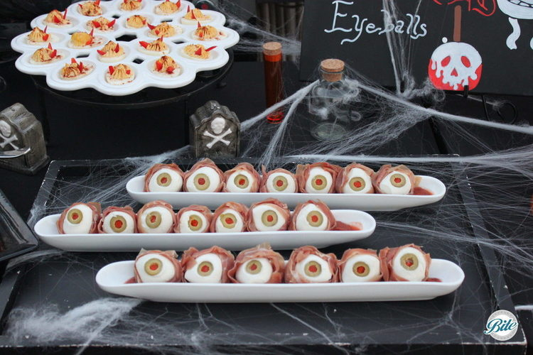 Bocconcini Eyeballs with prosciutto, olive, parma ham and bloody ooze.  Classic devilled egg with devil horns!  On a Halloween display with assorted tombstones, vials of blood, cobwebs...and all the other ghastly details