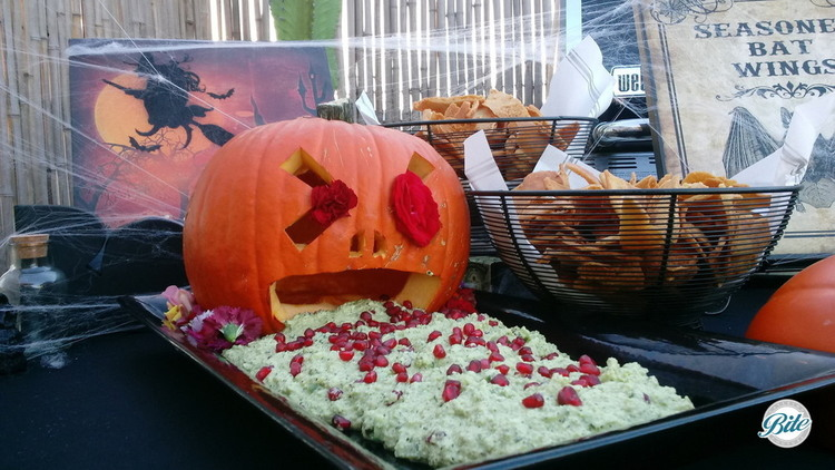 Pumpkin puke (edamame hummus) goes great with seasoned fried bat wings (pita chips) on a Halloween display. Our hand-carved puking pumpkin makes it look extra gross and we've decorated with cobwebs and a vial of something vile!