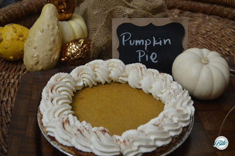 Pumpkin Pie with whipped cream and cinnamon.  On wood tray surrounded by holiday decor.