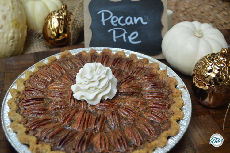 Pecan Pie with Whipped Cream. Set against wooden tray backdrop with holiday decor.